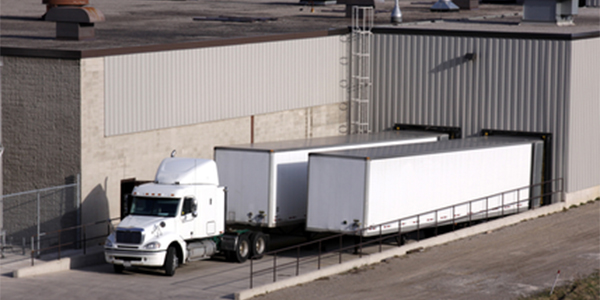 A transport truck getting loaded at a loading dock.
