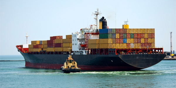 The small tugboat accentuates the size of the large container ship with cargo containers